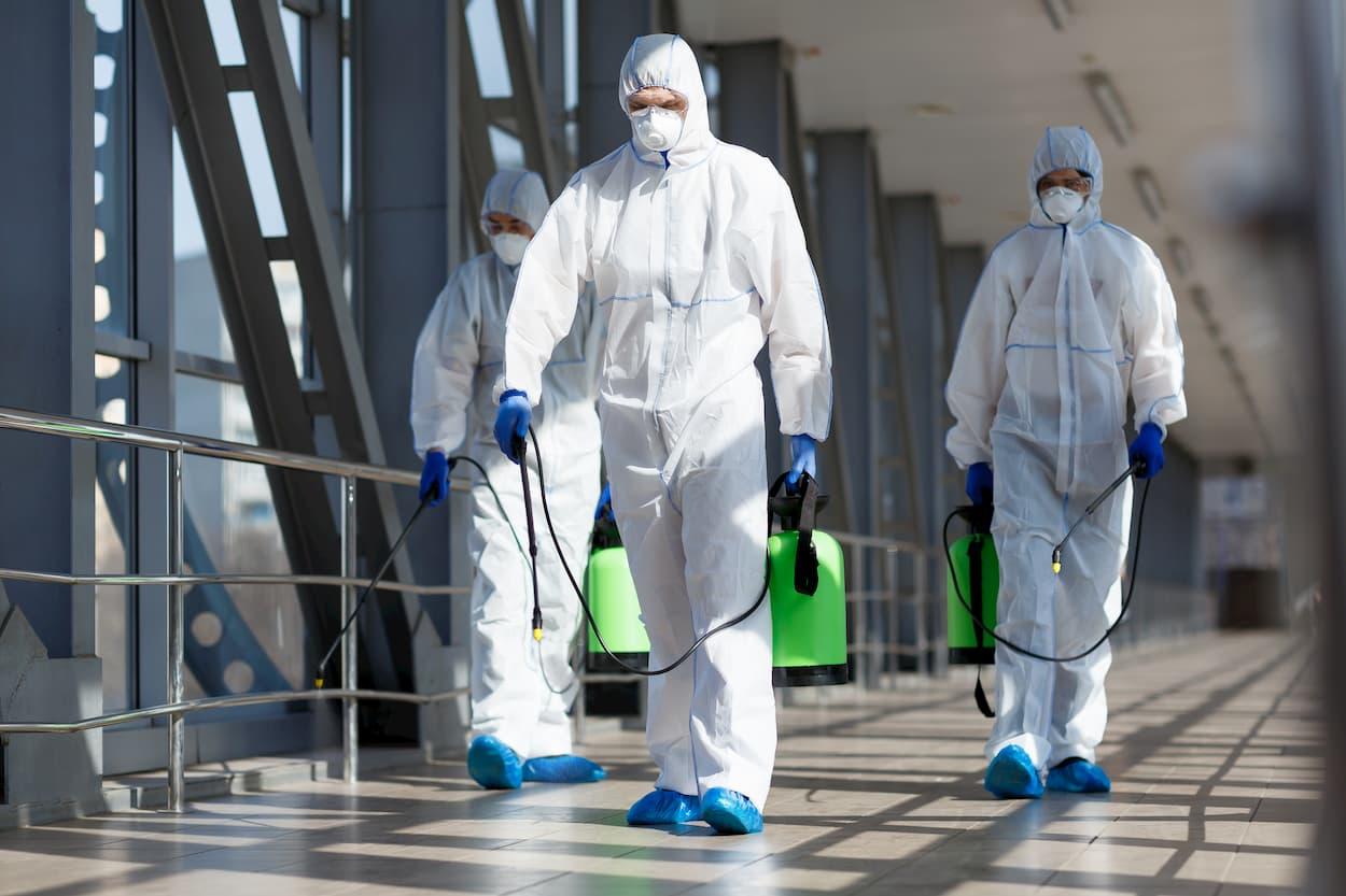 men in hazmat suits spraying a building