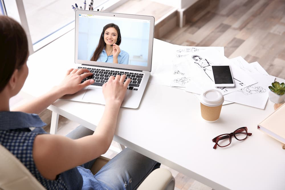 woman communicating with coworker via video conferencing