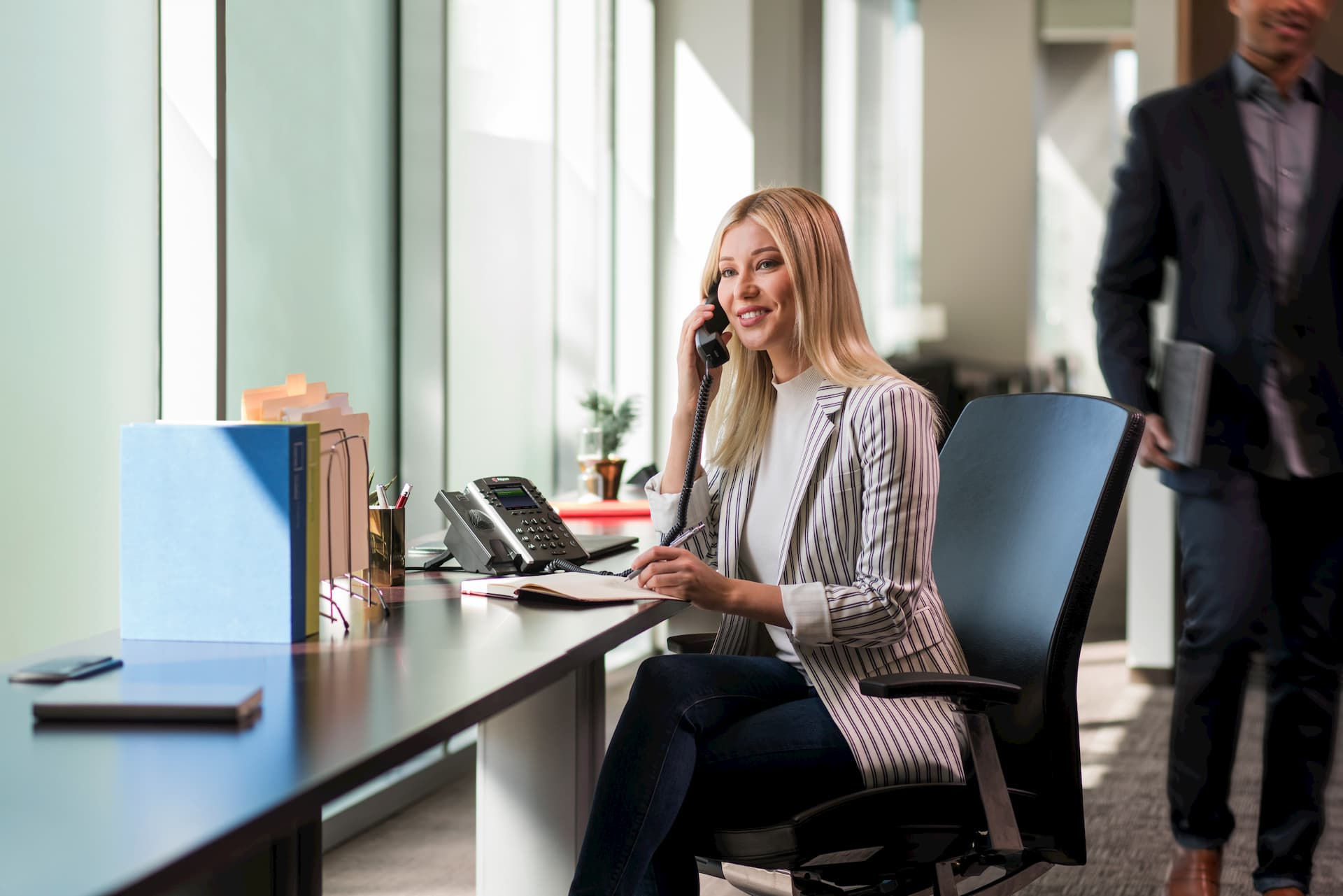 woman using Polycom phone in an open workplace