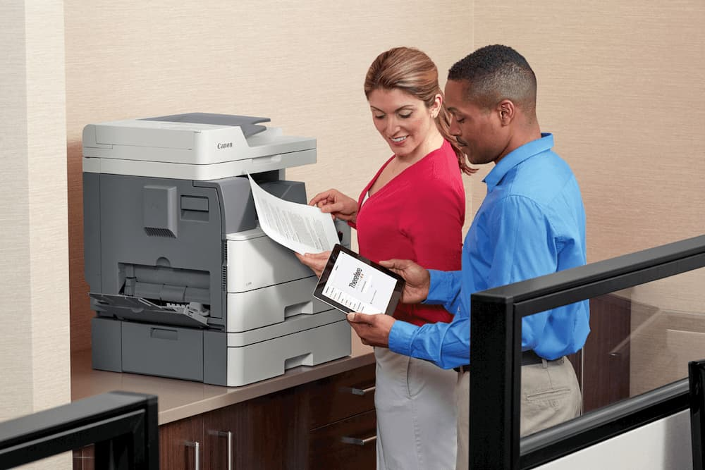 two coworkers getting documents off a workplace printer