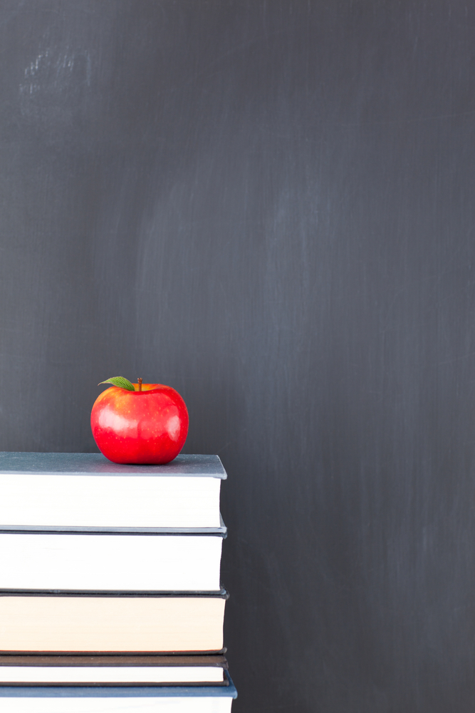 stack-of-books-with-red-apple-and-clean-blackboard.jpg