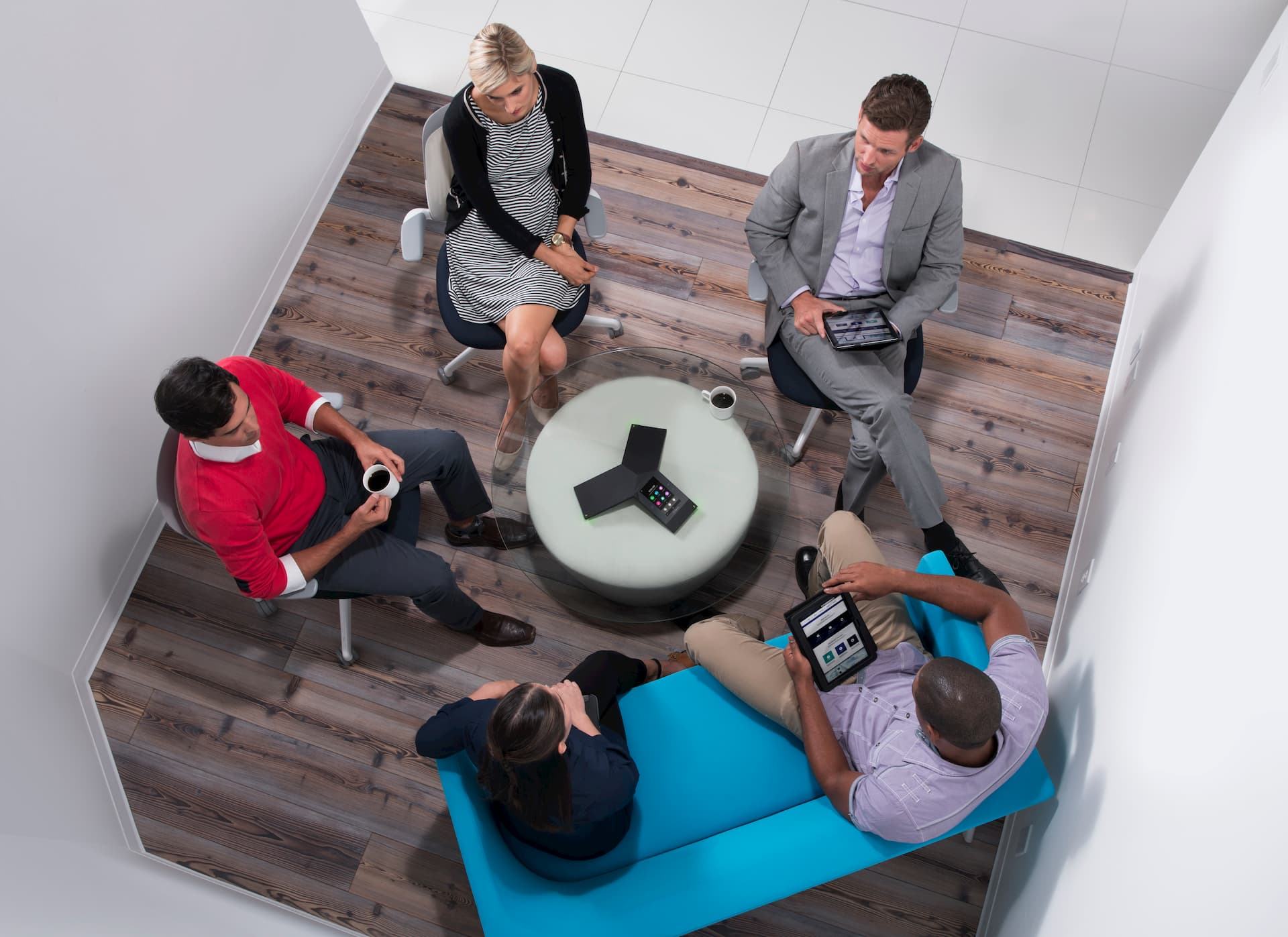 People collaborating around a Polycom conferencing solution