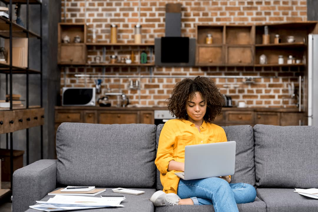 woman-working-from-home-on-a-laptop-wth-a-stack-of-papers