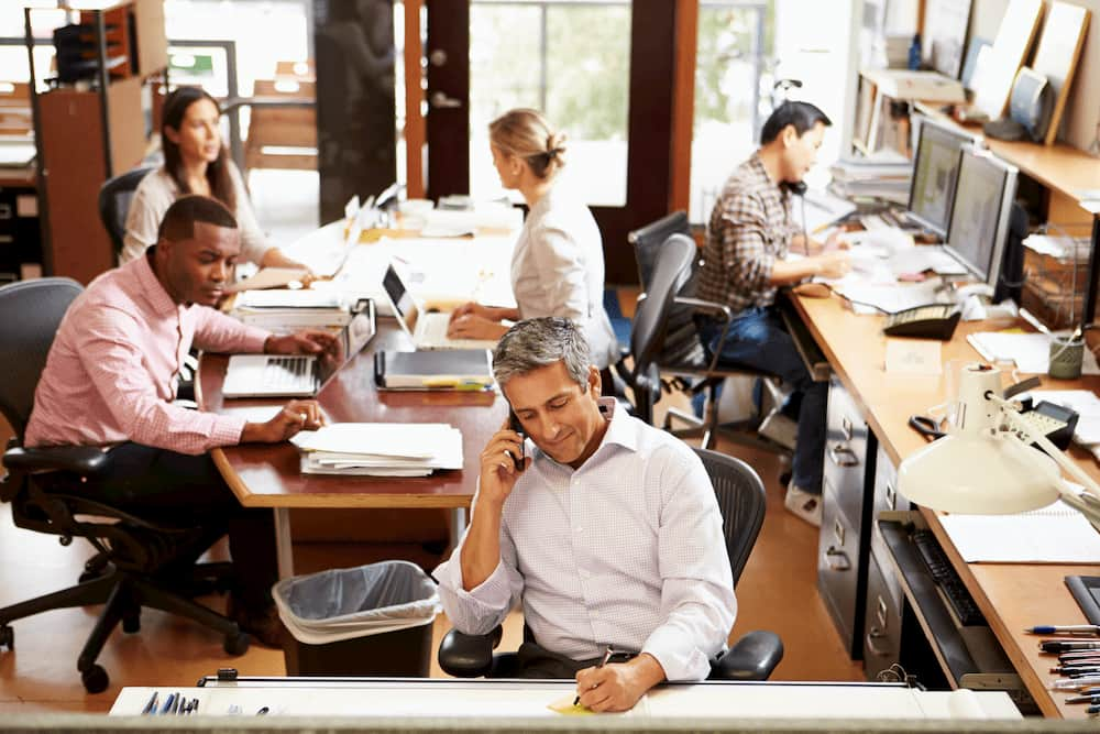 workers-in-office-setting-on-phone